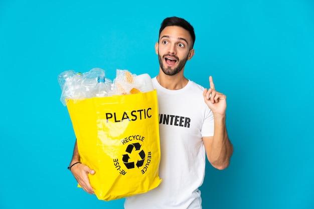 Jovem homem caucasiano segurando uma sacola cheia de garrafas plásticas para reciclar isoladas em um fundo azul pensando em uma ideia apontando o dedo para cima