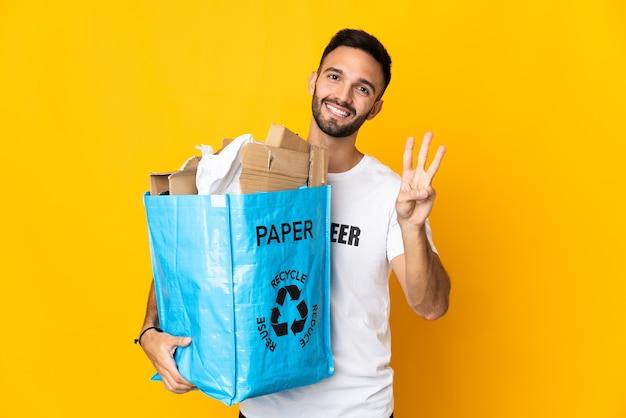 Jovem homem caucasiano segurando uma sacola cheia de papel para reciclar isolado no fundo branco feliz e contando três com os dedos