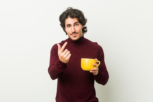 Jovem homem caucasiano segurando uma xícara de café, apontando com o dedo para você, como se convidando se aproximar.