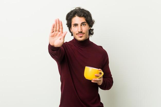 Jovem homem caucasiano segurando uma xícara de café em pé com a mão estendida, mostrando o sinal de stop, impedindo-o.