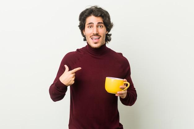Jovem homem caucasiano segurando uma xícara de café surpreendeu apontando para si mesmo, sorrindo amplamente.