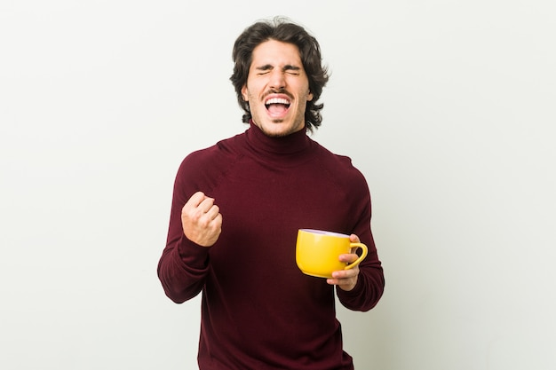 Jovem homem caucasiano segurando uma xícara de café torcendo despreocupado e animado