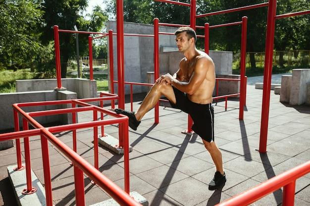 Jovem homem caucasiano sem camisa musculoso, fazendo exercícios de alongamento no parque num dia ensolarado de verão. treinar a parte superior do corpo ao ar livre. conceito de esporte, treino, estilo de vida saudável, bem-estar.
