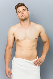 Jovem homem caucasiano sem camisa, vestindo uma toalha