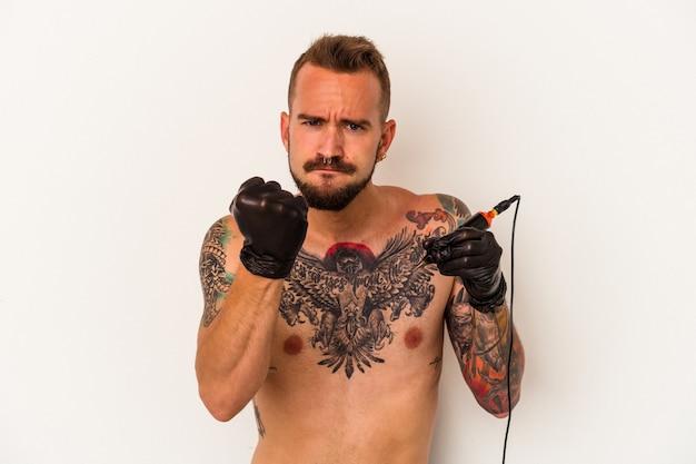 Jovem homem caucasiano sem t-shirt isolado no fundo branco, mostrando o punho para a câmera, expressão facial agressiva.
