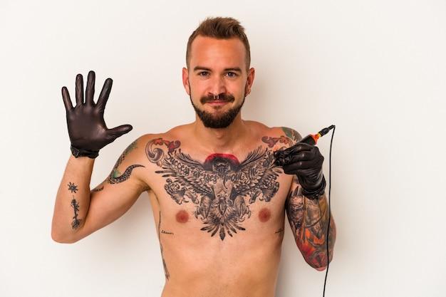 Jovem homem caucasiano sem t-shirt isolado no fundo branco, sorrindo alegre mostrando o número cinco com os dedos.