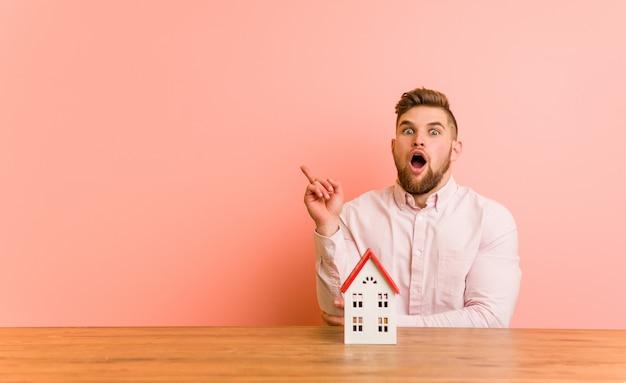 Jovem homem caucasiano sentado com um ícone de casa, tendo uma ótima idéia