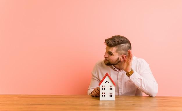 Jovem homem caucasiano sentado com um ícone de casa tentando ouvir uma fofoca.