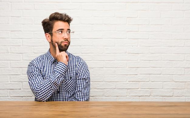 Jovem homem caucasiano sentado duvidando e confuso, pensando em uma idéia ou preocupado com algo