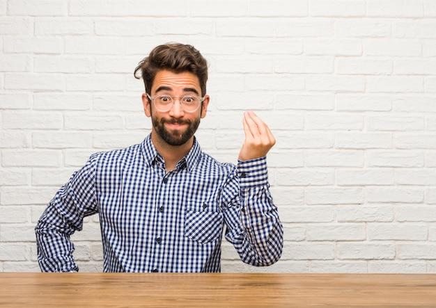 Jovem homem caucasiano sentado fazendo um gesto típico italiano, sorrindo e olhando para a frente, símbolo ou expressão com a mão, muito natural