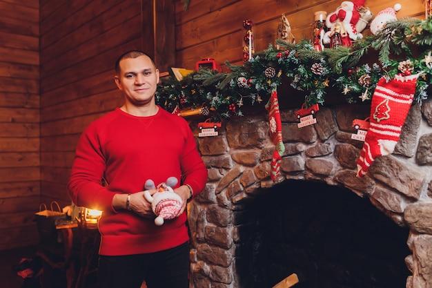 Jovem homem caucasiano sentado na lareira vestindo blusa segurando caneca perto de árvore de natal decorada.