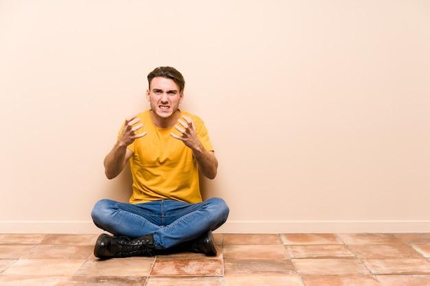 Jovem homem caucasiano sentado no chão isolado chateado gritando com as mãos tensas.