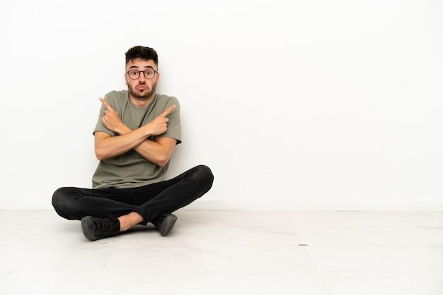 Jovem homem caucasiano sentado no chão, isolado no fundo branco, apontando para as laterais, tendo dúvidas
