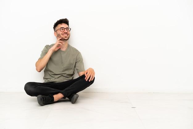 Jovem homem caucasiano sentado no chão, isolado no fundo branco, pensando em uma ideia enquanto olha para cima