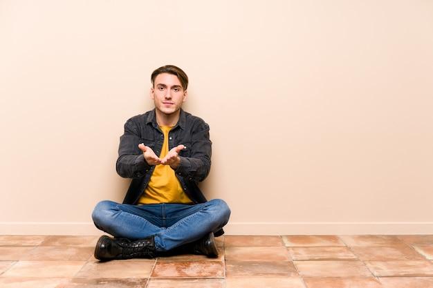 Jovem homem caucasiano sentado no chão isolado segurando algo com palm