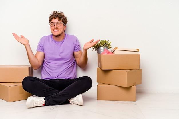 Jovem homem caucasiano sentado no chão pronto para mover-se isolado no fundo branco, duvidando e encolhendo os ombros em gesto de questionamento.