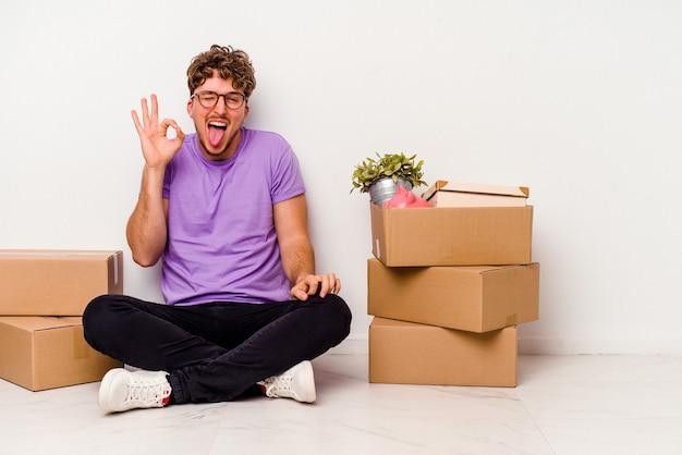 Jovem homem caucasiano sentado no chão, pronto para se mover, isolado na parede branca, pisca um olho e segura um gesto de ok com a mão.