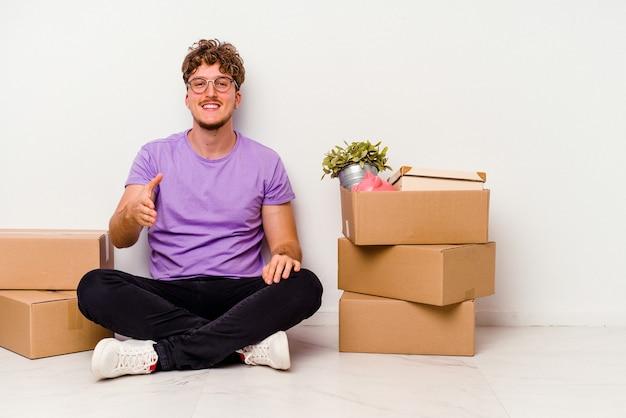 Jovem homem caucasiano sentado no chão, pronto para se mover, isolado no fundo branco, esticando a mão para a câmera em um gesto de saudação.