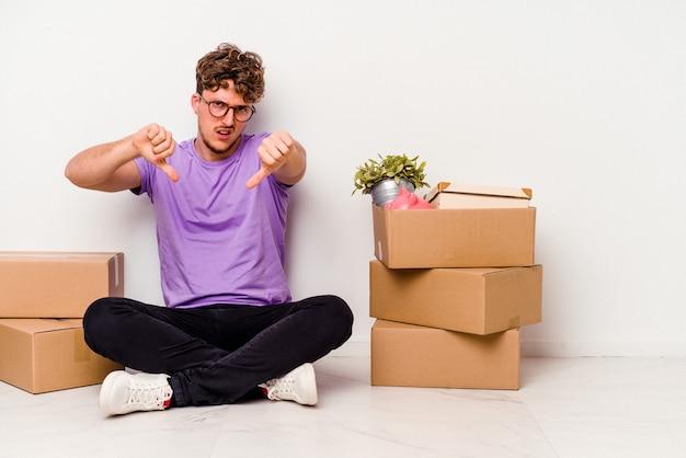 Jovem homem caucasiano sentado no chão, pronto para se mover, isolado no fundo branco, mostrando o polegar para baixo e expressando antipatia.