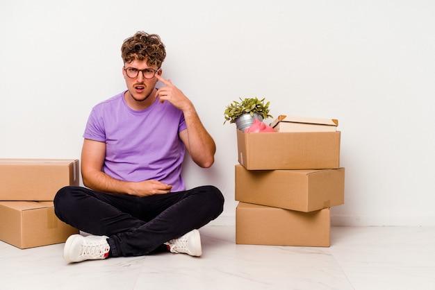Jovem homem caucasiano sentado no chão, pronto para se mover, isolado no fundo branco, mostrando um gesto de decepção com o dedo indicador.