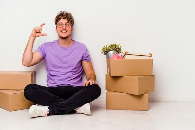 Jovem homem caucasiano sentado no chão pronto para se mover isolado no fundo branco, segurando algo pequeno com os indicadores, sorrindo e confiante.