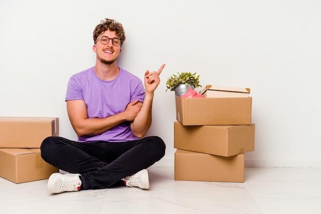 Jovem homem caucasiano sentado no chão pronto para se mover isolado no fundo branco, sorrindo alegremente, apontando com o dedo indicador para longe.