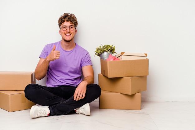 Jovem homem caucasiano sentado no chão, pronto para se mover, isolado no fundo branco, sorrindo e levantando o polegar