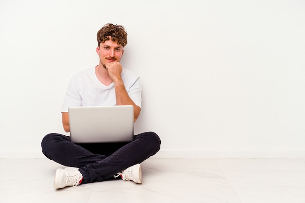 Jovem homem caucasiano sentado no chão segurando laptop isolado no fundo branco, sorrindo feliz e confiante, tocando o queixo com a mão.