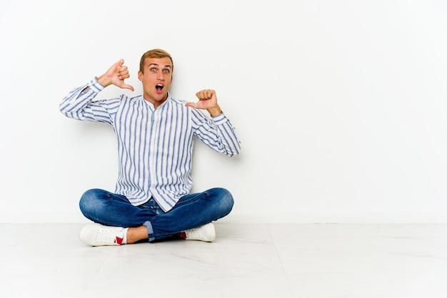 Jovem homem caucasiano sentado no chão sente-se orgulhoso e autoconfiante, exemplo a seguir.