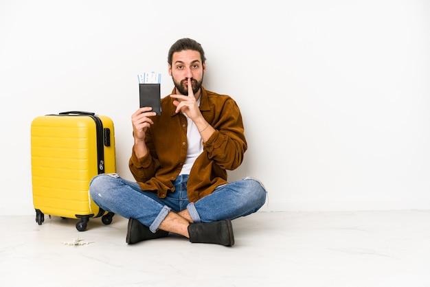 Jovem homem caucasiano sentado segurando um passaporte e uma mala isolada, mantendo um segredo ou pedindo silêncio.