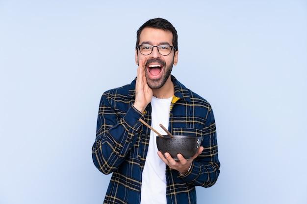 Jovem homem caucasiano sobre parede azul, gritando com a boca aberta, segurando uma tigela de macarrão com pauzinhos