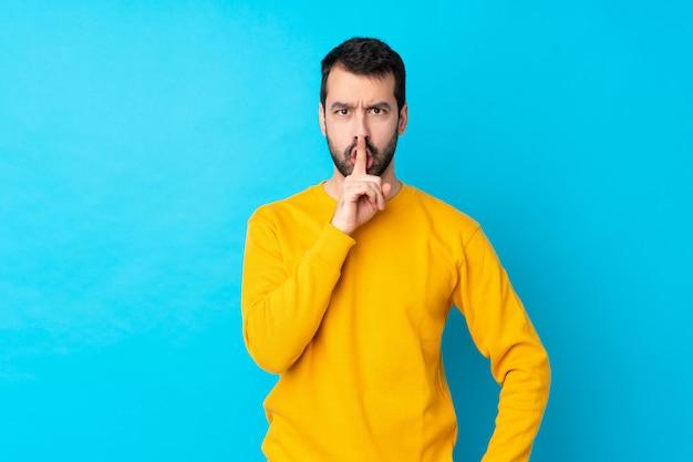 Jovem homem caucasiano sobre parede azul isolada, mostrando um sinal de gesto de silêncio colocando o dedo na boca