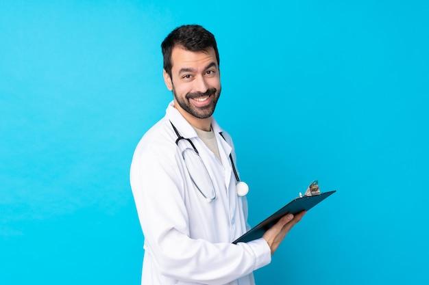 Jovem homem caucasiano sobre parede isolada, vestindo um vestido de médico e segurando uma pasta