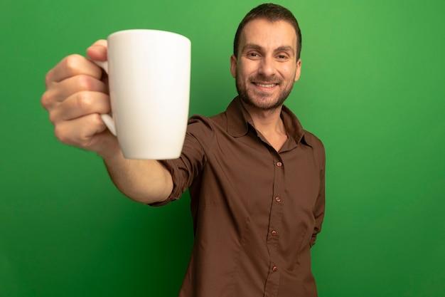 Jovem homem caucasiano sorridente, olhando para a câmera, estendendo a mão para uma xícara de chá em direção à câmera