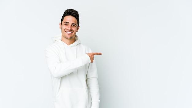 Jovem homem caucasiano sorrindo e apontando de lado, mostrando algo no espaço em branco.