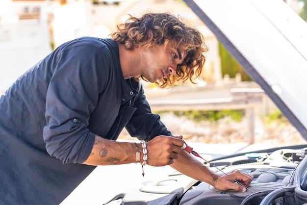 Jovem homem caucasiano tentando consertar um defeito em seu carro