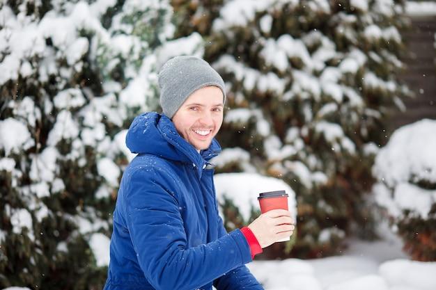 Jovem homem caucasiano tomando café no dia de inverno congelado ao ar livre