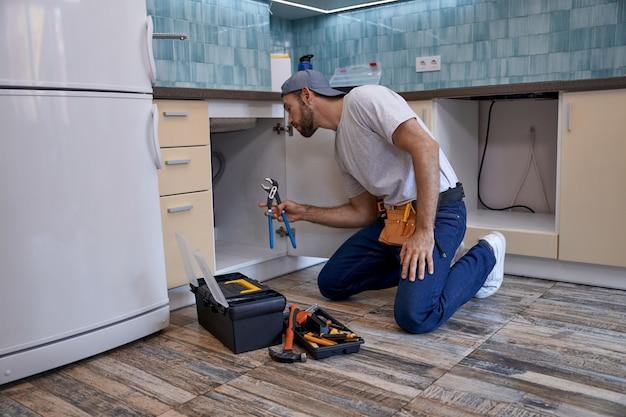 Jovem homem caucasiano trabalhando com uma chave inglesa na gaveta da cozinha