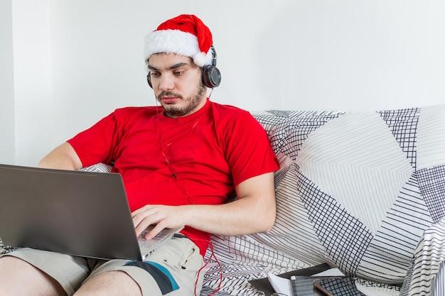 Jovem homem caucasiano trabalhando em casa durante a temporada de natal