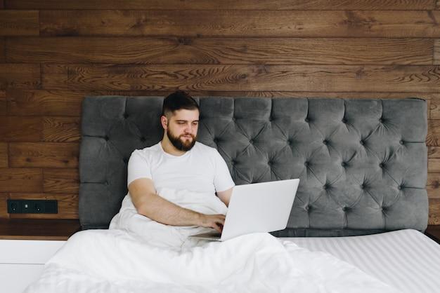 Jovem homem caucasiano trabalhando em seu laptop na cama de casa