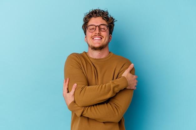 Jovem homem caucasiano usando óculos isolados em abraços azuis, sorrindo despreocupado e feliz.