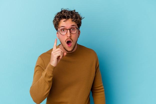 Jovem homem caucasiano usando óculos isolados em um fundo azul, tendo uma ideia, o conceito de inspiração.