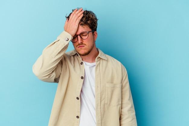 Jovem homem caucasiano usando óculos isolados na parede azul, esquecendo de algo, batendo na testa com a palma da mão e fechando os olhos.