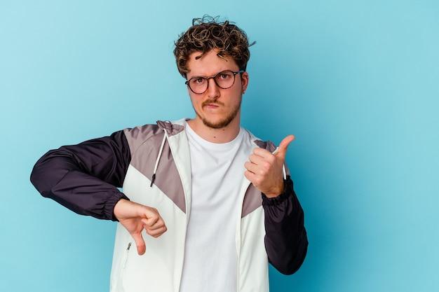 Jovem homem caucasiano usando óculos isolados na parede azul mostrando os polegares para cima e para baixo, é difícil escolher o conceito