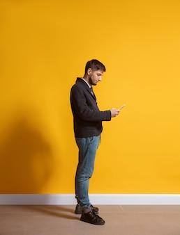 Jovem homem caucasiano usando retrato de corpo inteiro em smartphone sobre amarelo