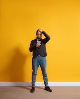 Jovem homem caucasiano usando smartphone com retrato de corpo inteiro isolado na parede amarela
