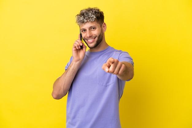 Jovem homem caucasiano usando telefone celular isolado em um fundo amarelo apontando para a frente com uma expressão feliz