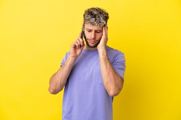 Jovem homem caucasiano usando telefone celular isolado em um fundo amarelo com dor de cabeça