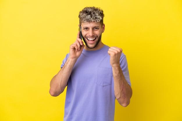 Jovem homem caucasiano usando telefone celular isolado em um fundo amarelo, comemorando a vitória na posição de vencedor