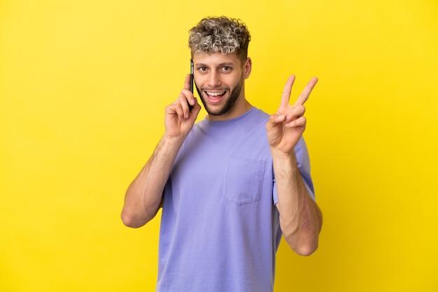 Jovem homem caucasiano usando telefone celular isolado em um fundo amarelo, sorrindo e mostrando sinal de vitória